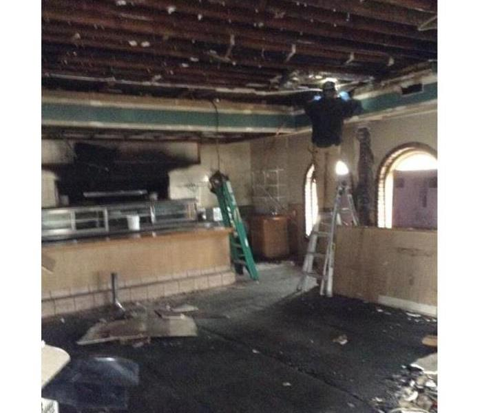 A restaurant with apparent fire damage and ripped out ceiling. SERVPRO workers are present